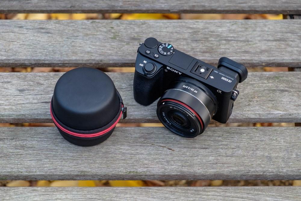 Объектив Samyang AF 35mm f/2.8 FE на камере Sony A6500 рядом с кофром