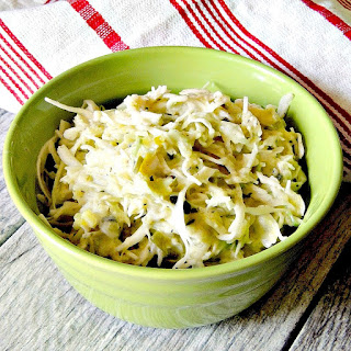 Dill Pickle Coleslaw in a green bowl with a red and white striped towel.