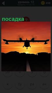 В свете заката происходит посадка самолета на аэродром