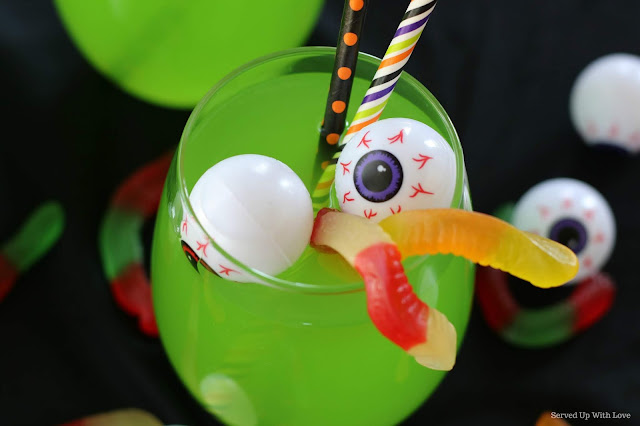 Clear glass with green punch on black background with eyeballs and gummy worms