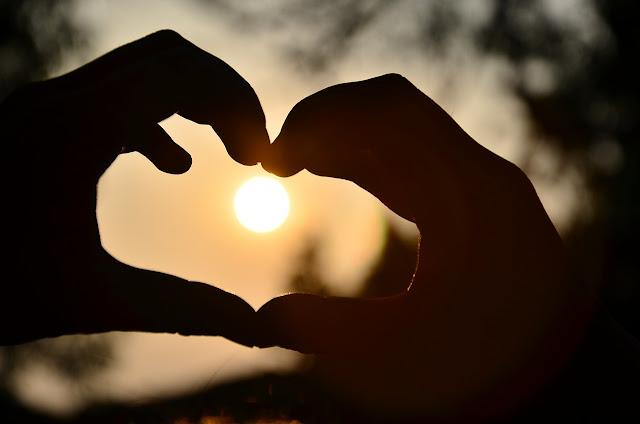 mit den Händen geformtes Herz im Gegenlicht