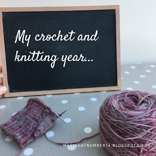 Blackboard saying 'my crochet and knitting year' and some hand-knit socks in the foreground