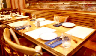 A long rectangular light brown table with lighter brown chairs with blue rectanuglar napkins and silver silverware on top of them on a bright background.