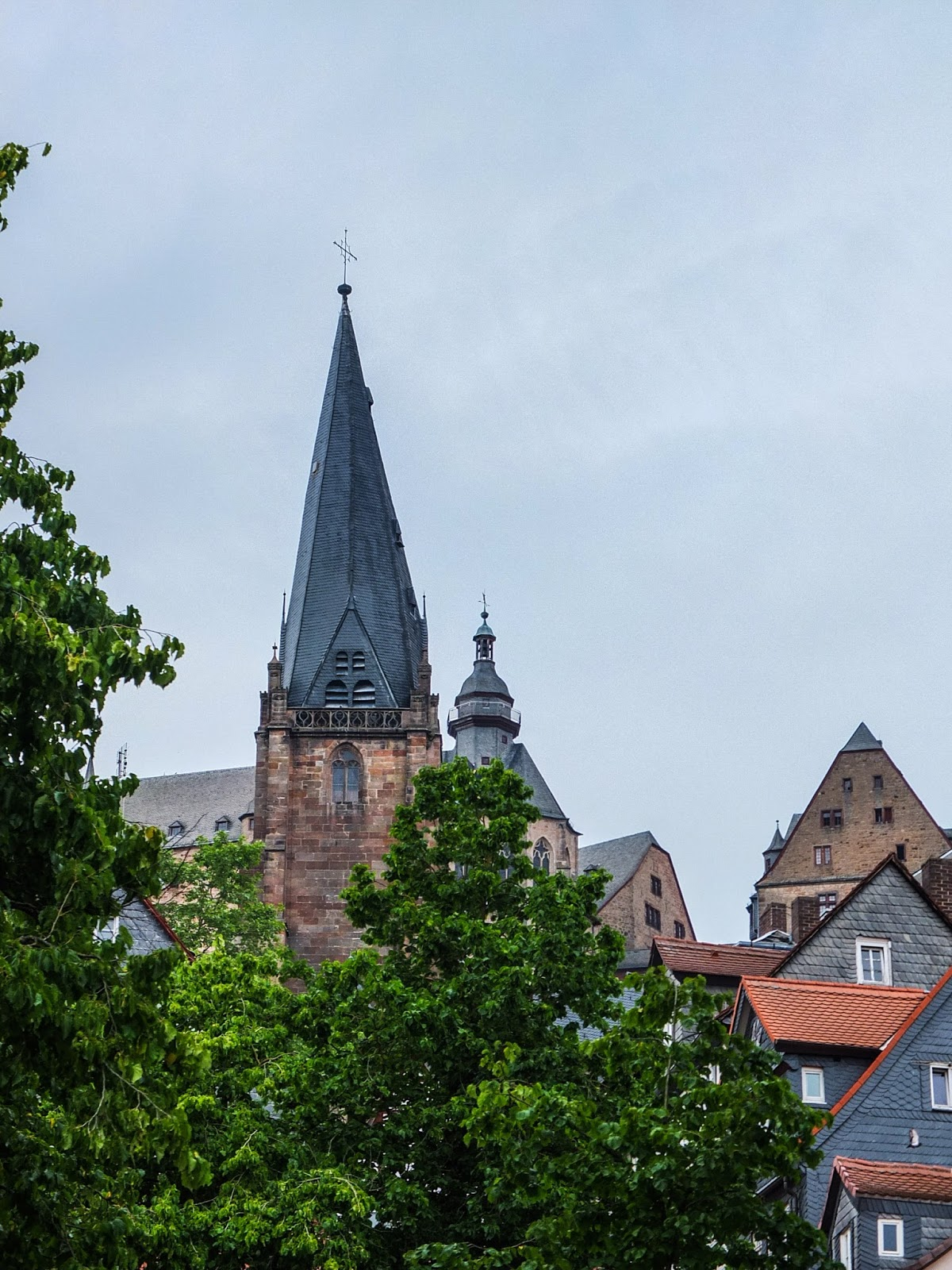 View of the St. Marienkirche church over the trees and buildings in Marburg.