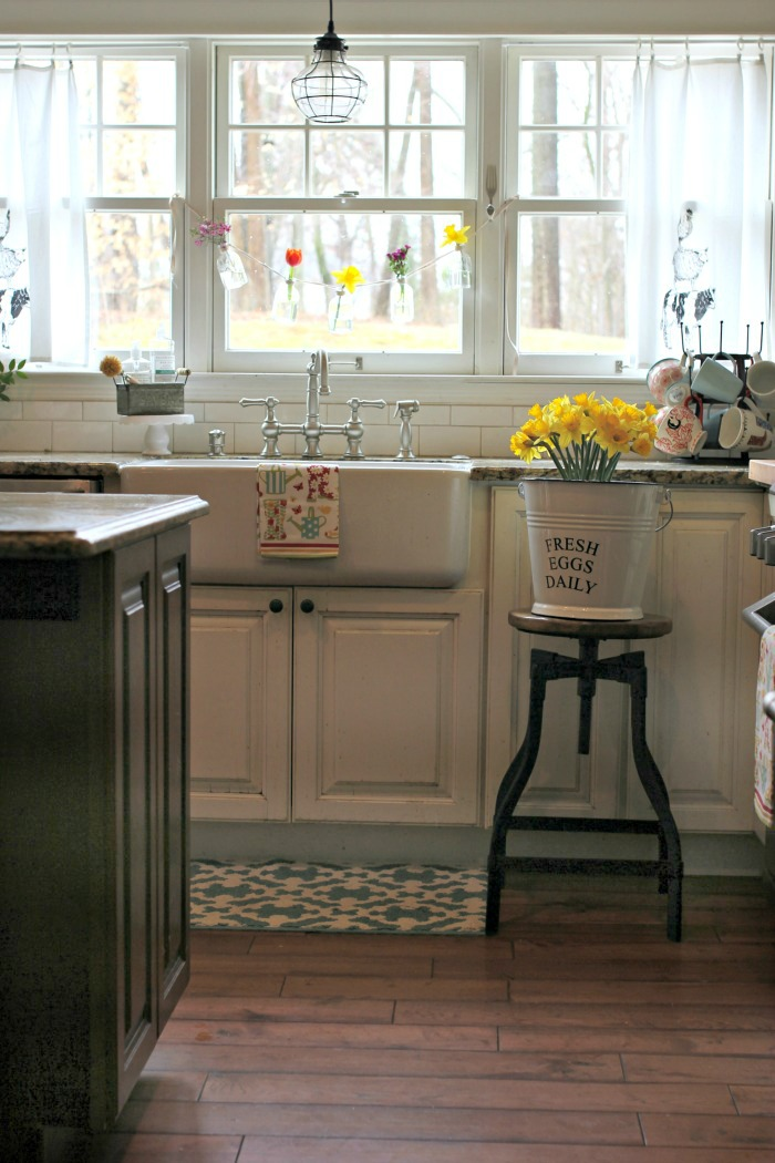 White kitchen with farmhouse sink and bottle garland with spring flowers - www.goldenboysandme.com