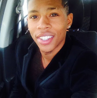 Yazz the Greatest wearing all black in a car