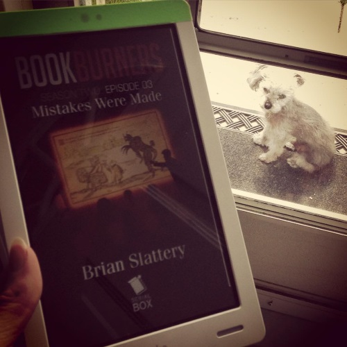 Murchie sits on a black mat just outside a screen door. He faces the viewer. One of his ears is flipped over. Inside, a pale hand holds a white Kobo with the cover of Bookburners S2 E3 on its screen. The cover features a presentation screen with a woodcut of a demon approaching a woman on it.