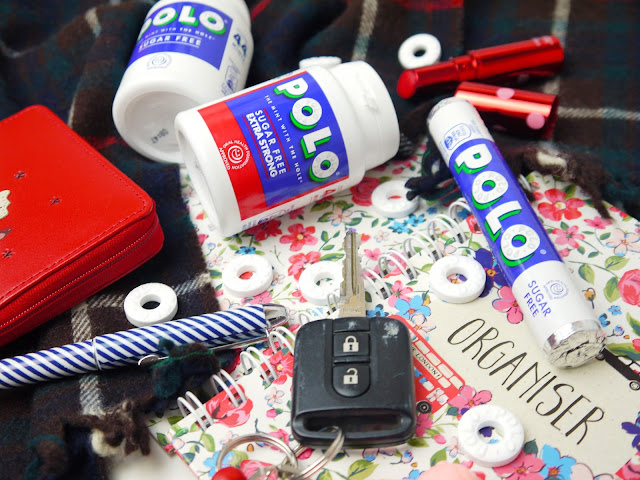 A tube of polos and two Polo share pots surrounded by handbag essentials such as purse, pen, keys, and diary