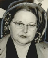 Headshot of a plump, dark-haired, middle-aged white woman wearing early 1950s style eyeglasses, hat, and hair wtyle