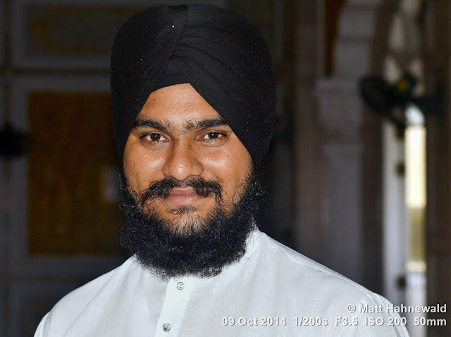 Matt Hahnewald Photography; Facing the World; photo; image; closeup; street portrait; headshot; indoor; world cultures; cultural; one person; character; personality; people; male; adult; powerful; strong; turban; Sikh; human; human face; human head; eyes; handsome; eye contact; photography; consent; empathy; rapport; portrait; portraiture; environmental portrait; travel portrait; travel destination; colour; 4 : 3 aspect ratio; horizontal format; posing; Thailand; Bangkok; Asia; Southeast Asia; Nikon D3100; Nikkor AF-S 50mm f/1.8G; prime lens; 50 mm; travel; religion; en face; front view; city dweller; tradition; manly; facial expression; black turban; Phra Nakhon District; ethnic; ethnic minority; Gurudwara Siri Guru Singh Sabha; Little India