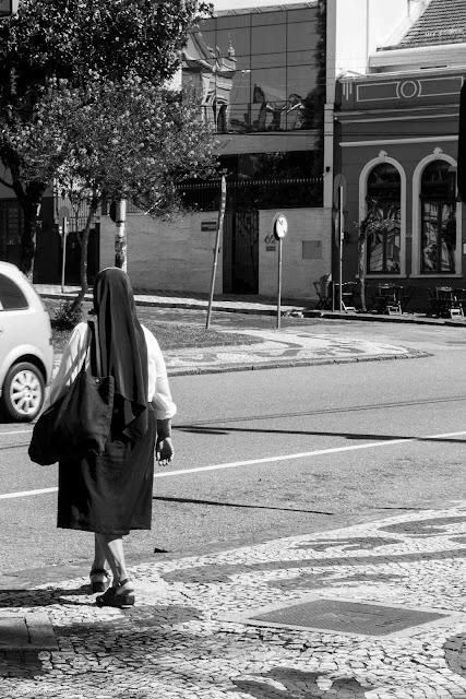 religiosa na calçada prestes a atravessar a rua