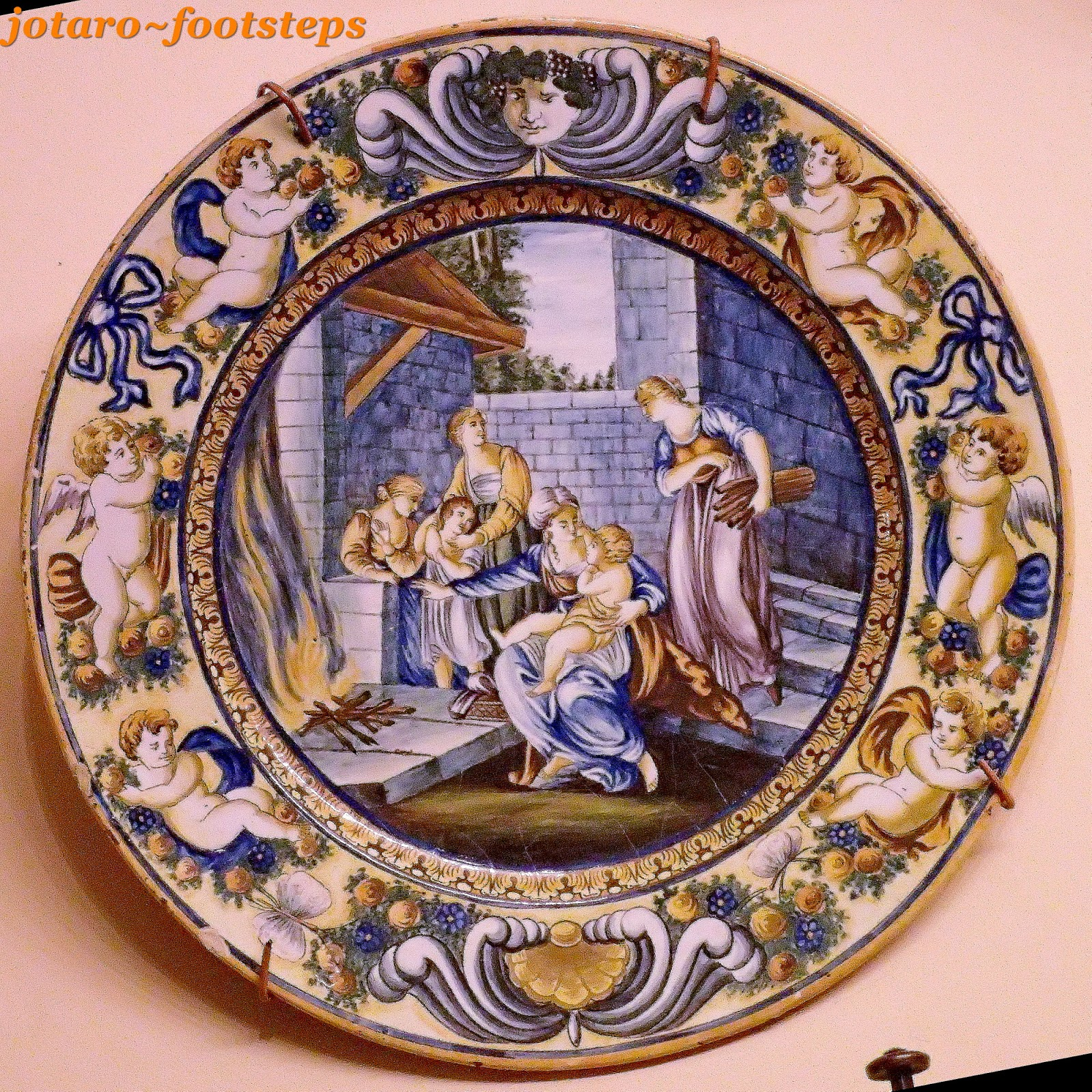 Glazed porcelain plate with scenery of a medieval family ringed by cherubs.
