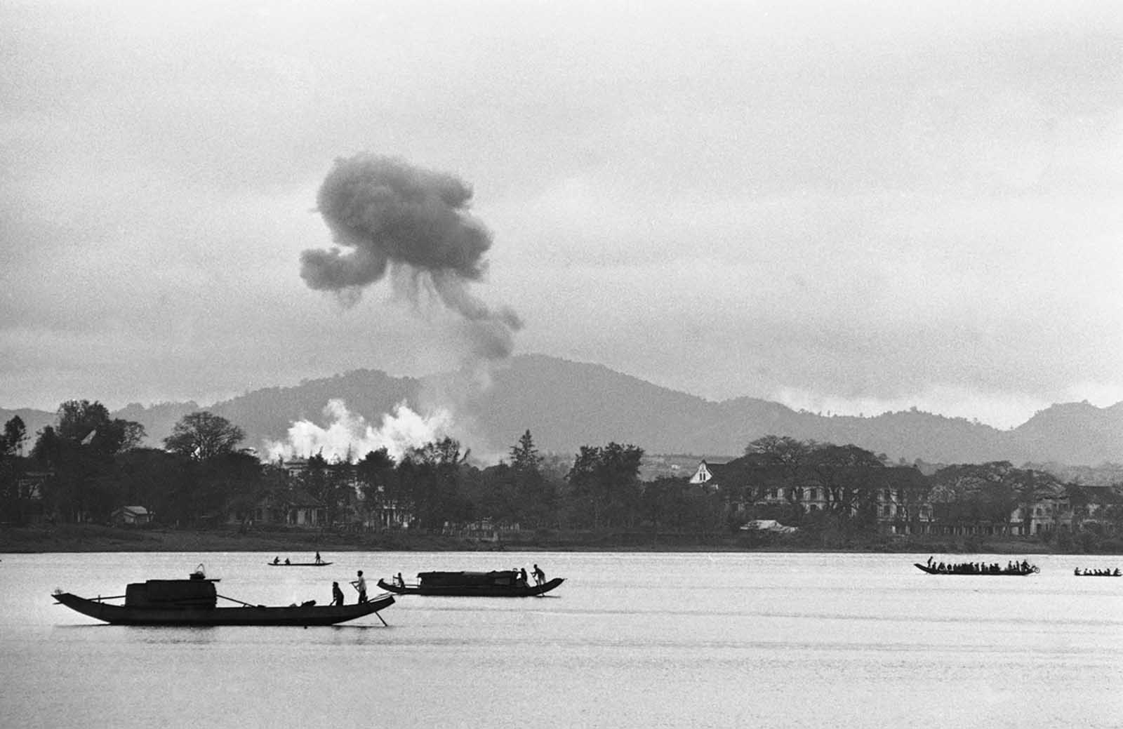 Napalm air strikes raise clouds into gray monsoon skies as houseboats glide down the Perfume River toward Hue in Vietnam on February 28, 1963, where a battle for control of the old Imperial City ended with a Communist defeat. Firebombs were directed against a village on the outskirts of Hue.
