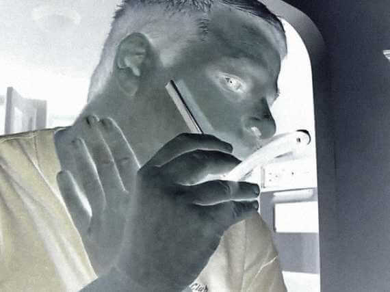 negative image of man dry shaving with old-fashioned straight razor
