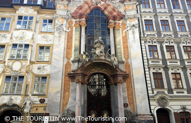 Giant ornate entrance door of a church on a pedestrian street.