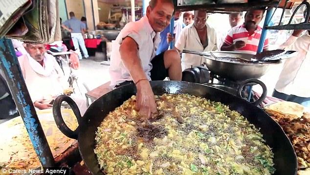 Indijski kuhar gole ruke stavlja u 200 stepeni Celzijusa vrelo ulje.