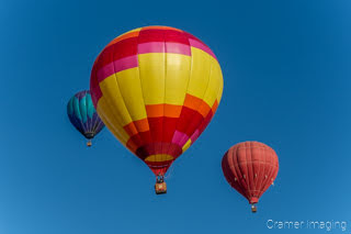 Cramer Imaging's fine art photograph of three colorful hot air balloons taking flight in Panguitch Utah with a blue morning sky