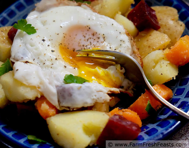 Image of a plate of roasted beets, carrots, and potatoes on a bed of spinach topped with a fried egg.