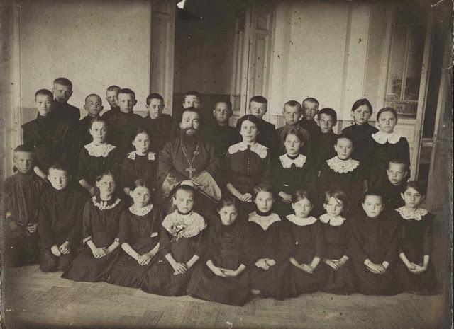 Крестьянские дети села Рыбацкое - ученики церковно-приходской школы, окружившие священника Николая Кулигина.