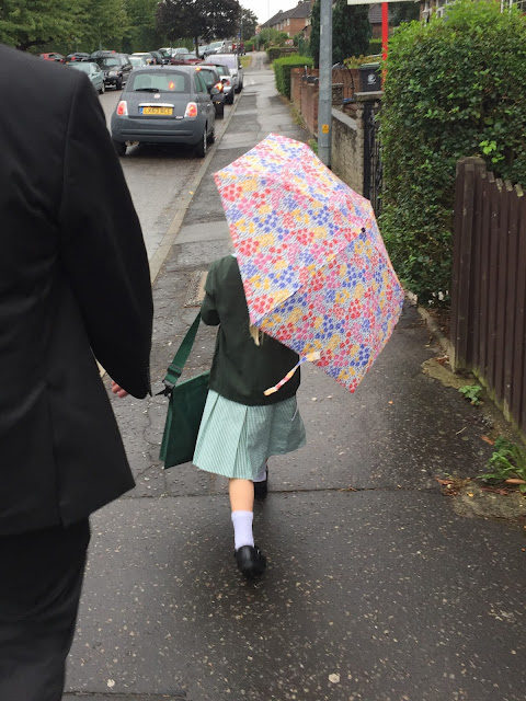 A girl in school uniform holding an umbrella seen from behind walking away