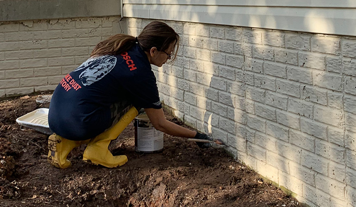 Cristina Garay painting foundation wall with Behr Masonry, Stucco & Brick Paint
