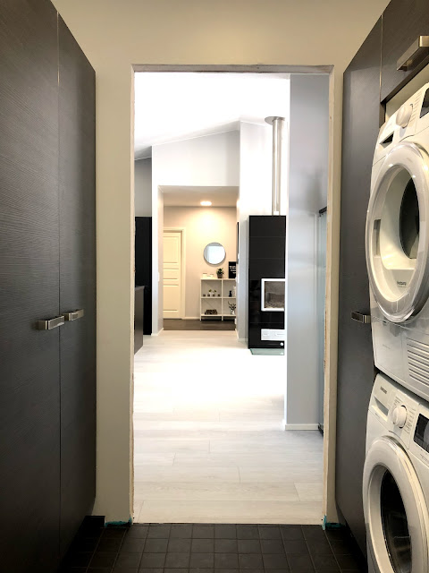kodinhoitohuone, pesukone, kuivausrumpu, pesutorni, musta takka, harmaa kodinhoitohuone, pergo, vinyylilankku, takaneduslasi