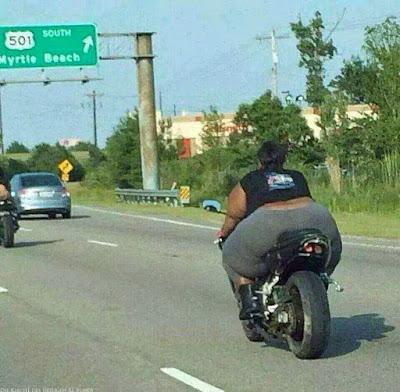 Sehr dicke schwarze Frau in Leggings auf Motorrad lustig