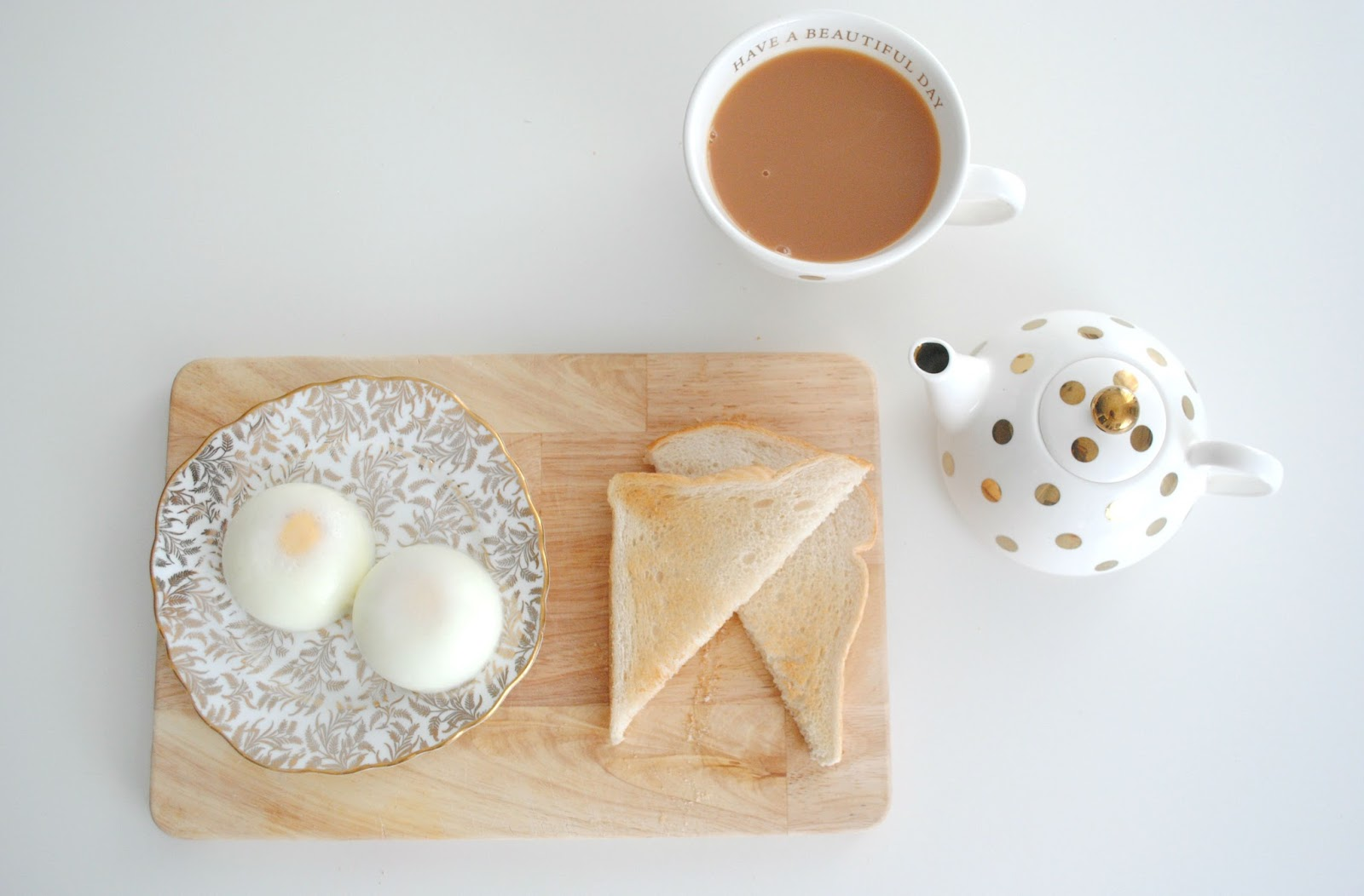 poached eggs gold tea teapot polka dots wooden board breakfast