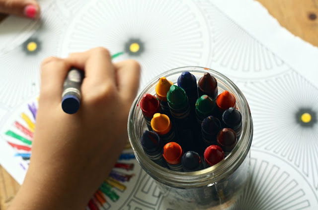 Child with good study habits using crayon to color book