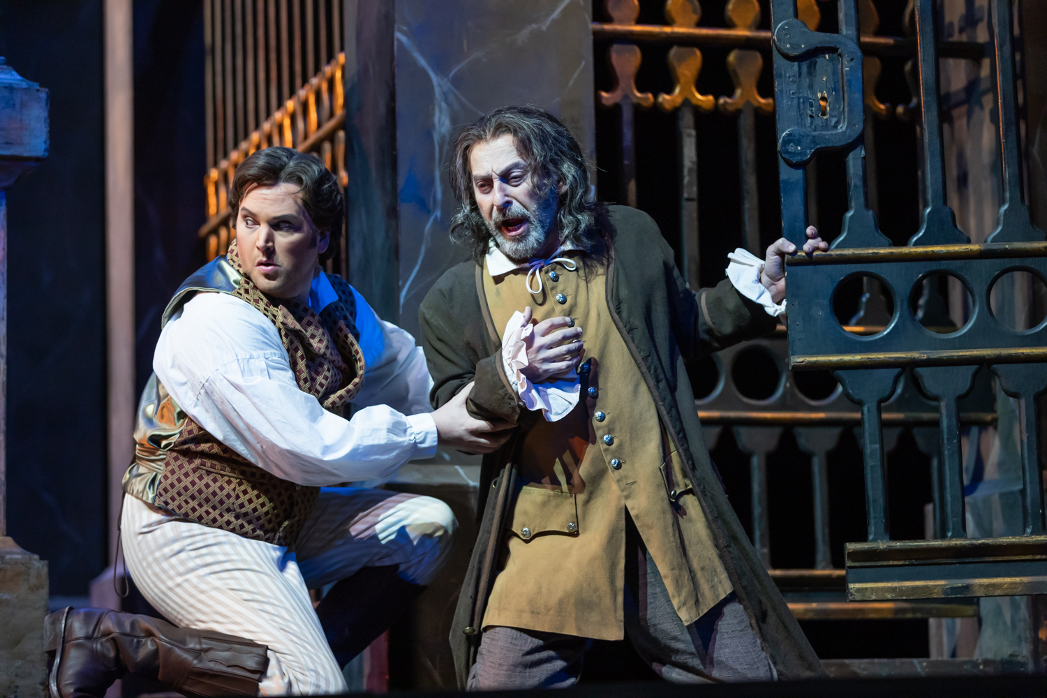 IN REVIEW: tenor SCOTT QUINN as Cavaradossi (left) and bass-baritone SABRI KARABUDAK as Angelotti (right) in North Carolina Opera's April 2019 production of Giacomo Puccini's TOSCA [Photograph by Eric Waters, © by North Carolina Opera]