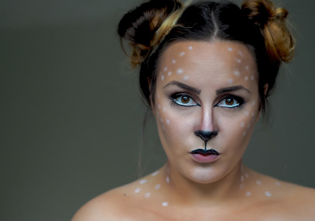 close up of a deer inspired makeup look using black paint for a nose and mouth and around the eyes and then white bits for the spots of the deer