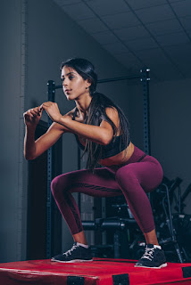 A lady performing the squat exercise