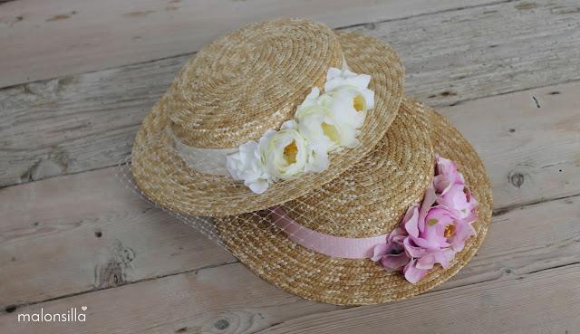 Dos sombreros con flores, uno en blanco y el otro en rosa palo