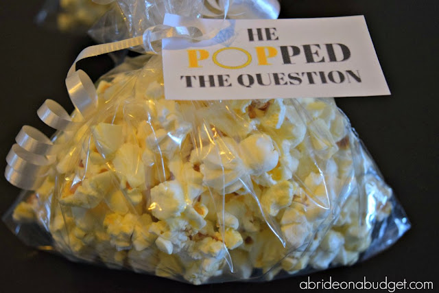Here's a FUN and cheap engagement party favor. Use popcorn and make these He Popped The Question Engagement Party Favors from www.abrideonnabudget.com. Even better, you can get the printable tag for FREE in the blog post!