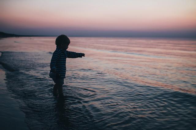 Niño junto al mar, a las olas, junto a sus sueños, niñez, inocencia y atardecer