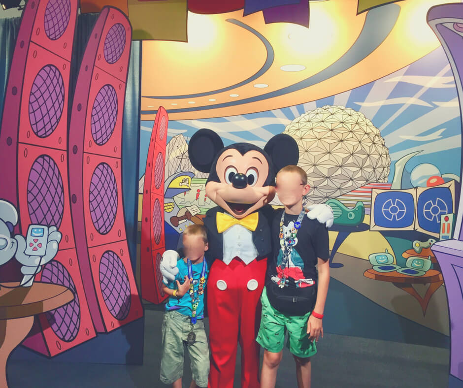 Two boys have a photo with Mickey Mouse at Epcot, Walt Disney World