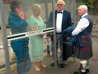 Two couples in formal wear waiting at a bus stop, Edinburgh, Scotland