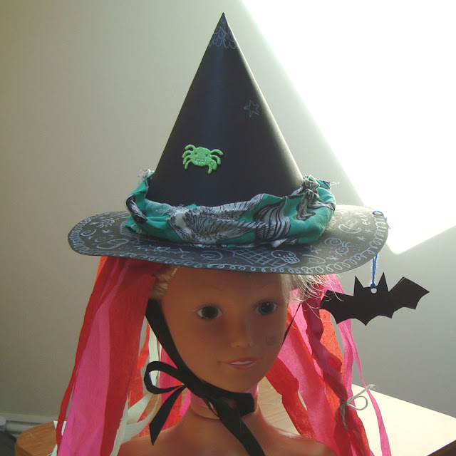 A witches hat made out of two sheets of A3 black card and decorated with crepe paper, scrap fabric, stickers and white pencil.