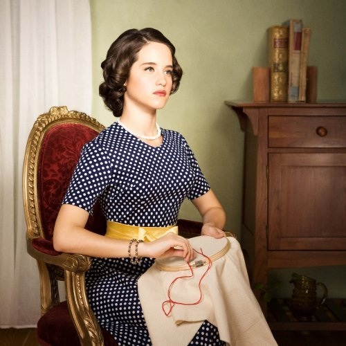 Ximena Sariñana posed stiffly in a fine chair dressed and coiffed in vintage 1950s style while sewing with red thread