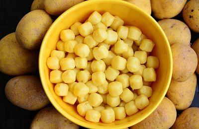 Receta de ñoquis con salsa de queso. Pasta sin cocer en un recipiente, sobre las papas con cáscara.