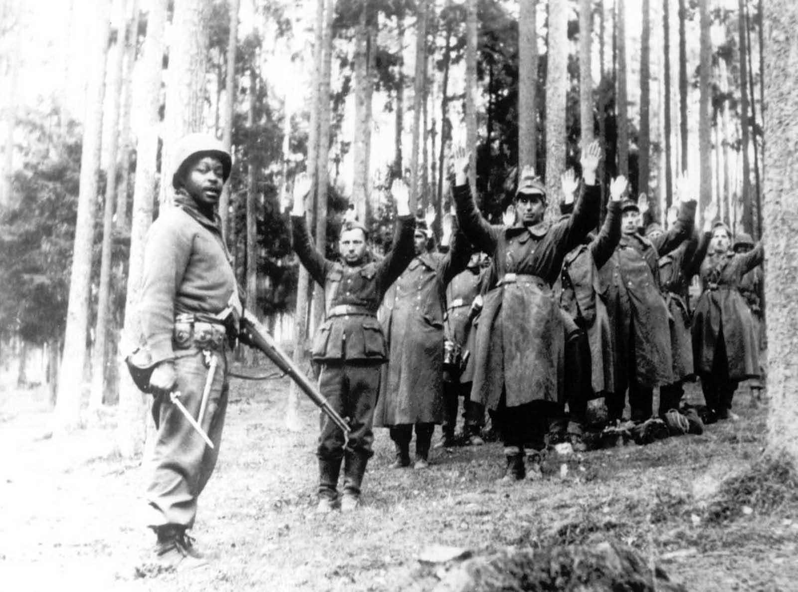 An American soldier of the 12th Armored Division stands guard over a group of German soldiers, captured in April 1945, in a forest at an unknown location in Germany.