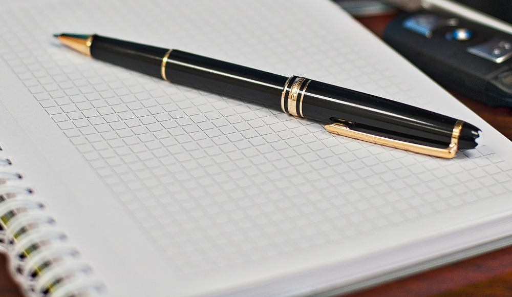 Black and golden pen resting on top of an open empty journal