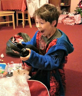 Boy with happy face, opening a Christmas present.