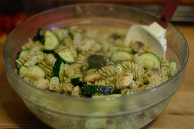 All of the ingredients for the Chicken Pesto Pasta Salad being tossed together in a bowl.