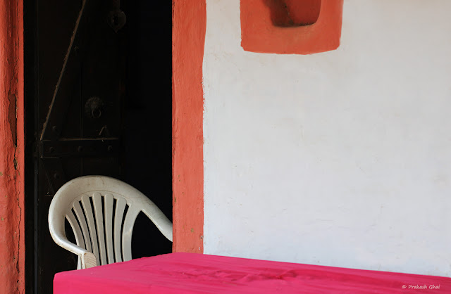 A partially visible White Chair placed in front of an open brown door at The Village area at Jawahar Kala Kendra, Jaipur, India.
