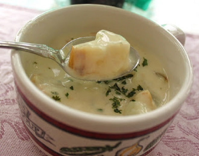 this is a white creamy bowl of potato soup with italian spices and herbs