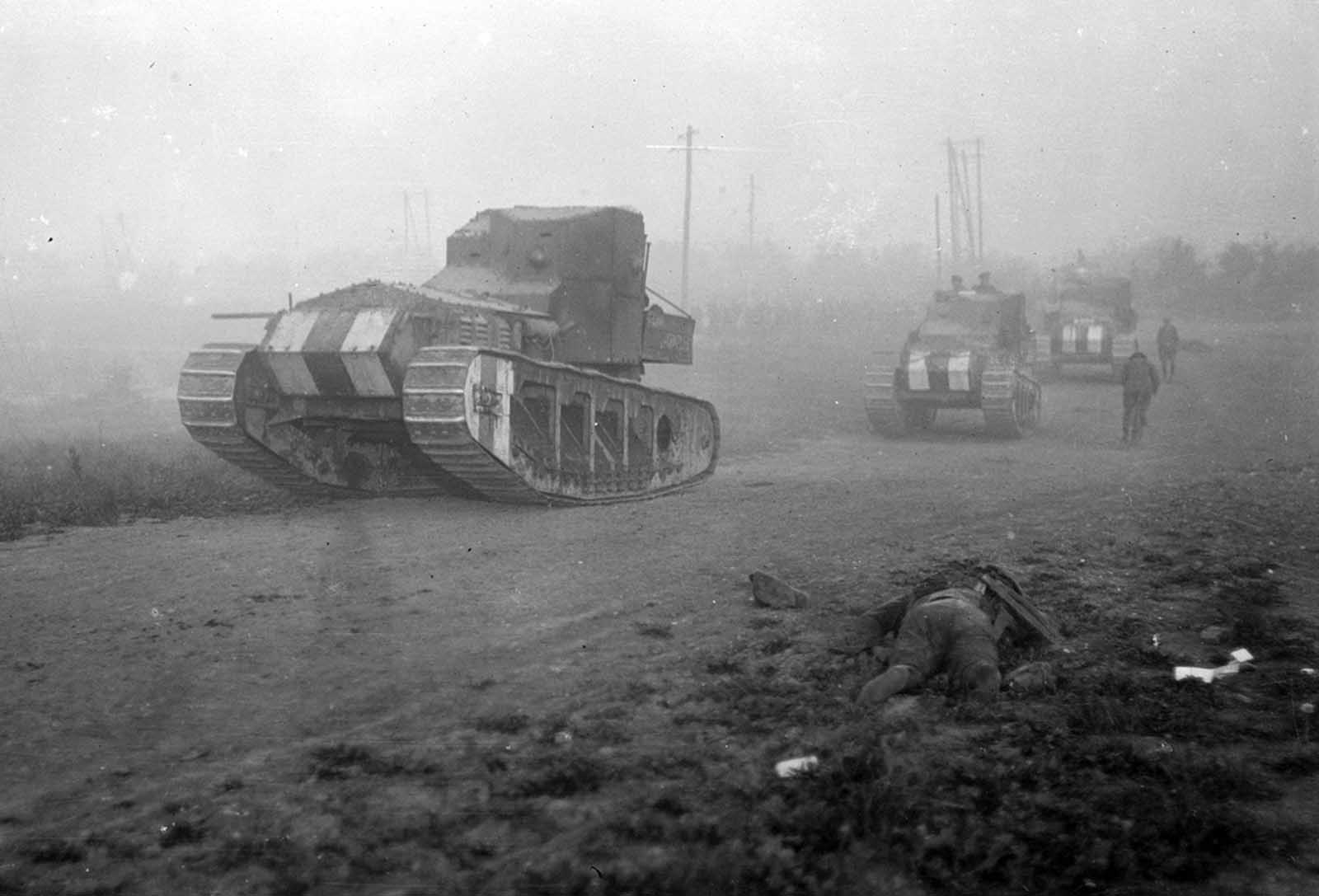 British Medium Mark A Whippet tanks advance past the body of a dead soldier, moving to an attack along a road near Achiet-le-Petit, France, on August 22, 1918. The Whippets were faster and lighter than previously deployed British heavy tanks.