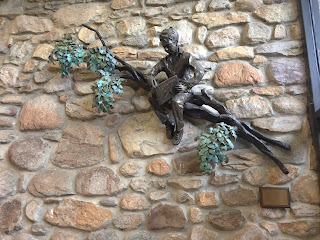Bronze sculpture of small boy on tree branch reading a book