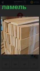 В помещении стопкой стоят ламели, пластины из различных материалов дерева, перевязанные скотчем