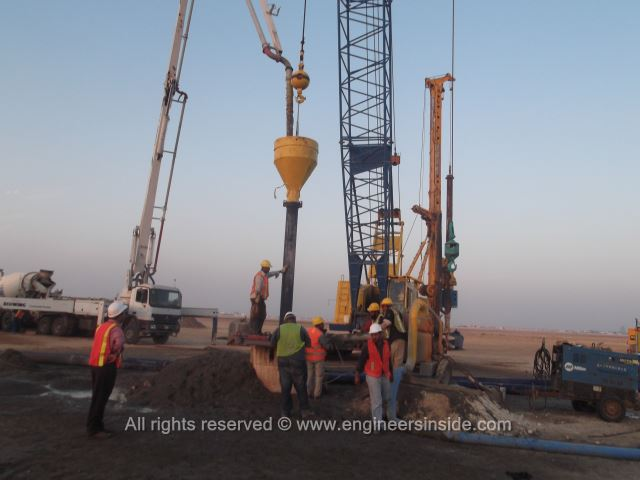 Workers pouring concrete into test pile